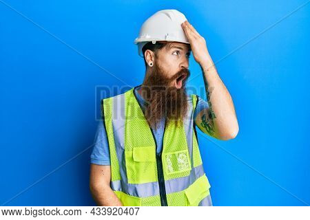 Redhead man with long beard wearing safety helmet and reflective jacket surprised with hand on head for mistake, remember error. forgot, bad memory concept.