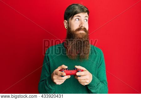 Redhead man with long beard playing video game holding controller smiling looking to the side and staring away thinking.