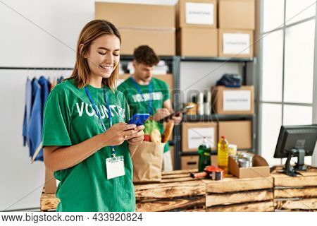Young hispanic volunteer couple working at charity center. Woman smiling happy using smartphone.