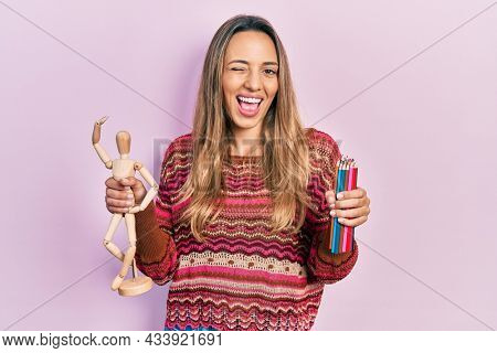 Beautiful hispanic woman holding small wooden manikin and colored pencils winking looking at the camera with sexy expression, cheerful and happy face.