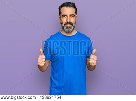 Middle aged man with beard wearing casual blue t shirt success sign doing positive gesture with hand, thumbs up smiling and happy. cheerful expression and winner gesture.