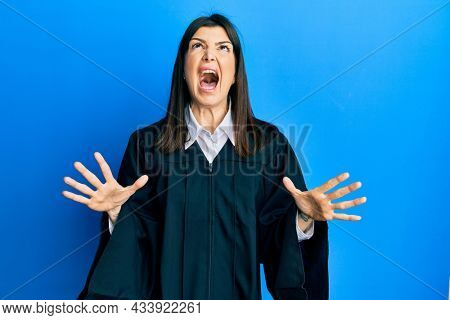 Young hispanic woman wearing judge uniform crazy and mad shouting and yelling with aggressive expression and arms raised. frustration concept.