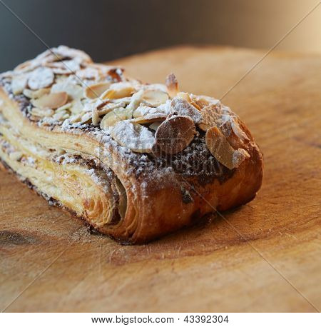 Fresh chocolate and Almond rollover croissant pastry sprinkled with icing sugar on a brown wooden serving board with copy space - Shallow Depth of Field (DOF) poster