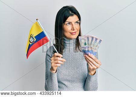 Young hispanic woman holding colombia flag and colombian pesos banknotes smiling looking to the side and staring away thinking.