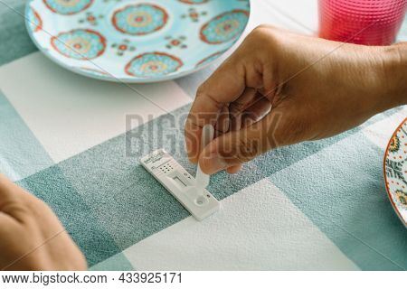 a young caucasian man is doing a covid-19 rapid test by placing his own sample into the covid-19 antigen diagnostic test device, at a table set for lunch
