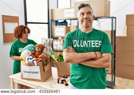 Middle age man wearing volunteer t shirt at donations stand smiling looking to the side and staring away thinking.
