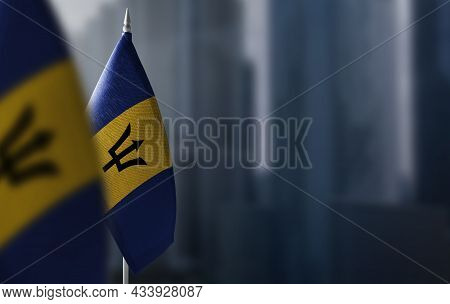 Small Flags Of Barbados On A Blurry Background Of The City