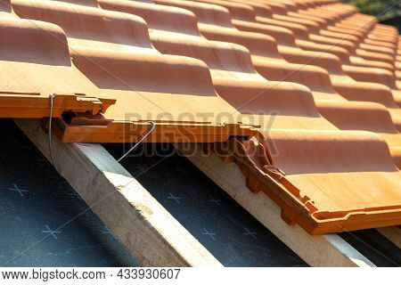 Closeup Of Metal Montage Anchor For Installation Of Yellow Ceramic Roofing Tiles Mounted On Wooden B