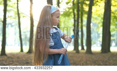 Little Happy Child Girl Blowing Soap Bubbles Outside In Green Park. Outdoor Summer Activities Concep