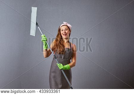 Funny Housewife Cleaning Around With A Mop On A Gray Background. Comical Female Washer Holding Mop.