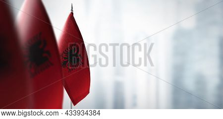 Small Flags Of Albania On A Blurry Background Of The City