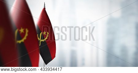 Small Flags Of Angola On A Blurry Background Of The City