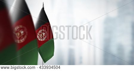 Small Flags Of Afghanistan On A Blurry Background Of The City