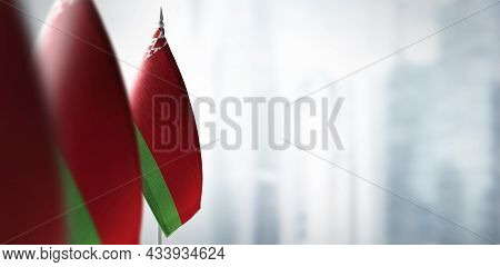 Small Flags Of Belarus On A Blurry Background Of The City