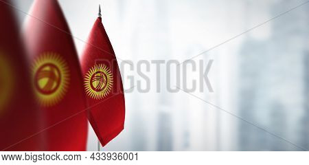 Small Flags Of Kirghizia On A Blurry Background Of The City