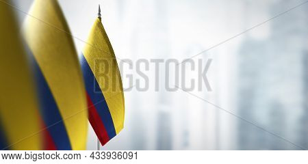 Small Flags Of Colombia On A Blurry Background Of The City