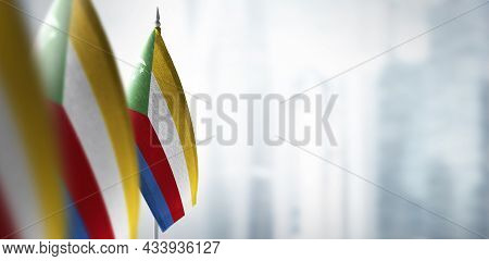 Small Flags Of Comoros On A Blurry Background Of The City