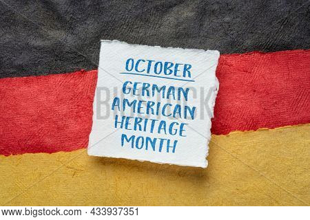 October - German American Heritage Month, square note against paper abstract in colors of Germany national flag, reminder of cultural event