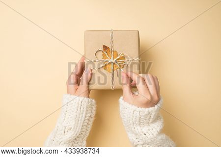 First Person Top View Photo Of Female Hands In White Sweater Unpacking Craft Paper Giftbox With Twin