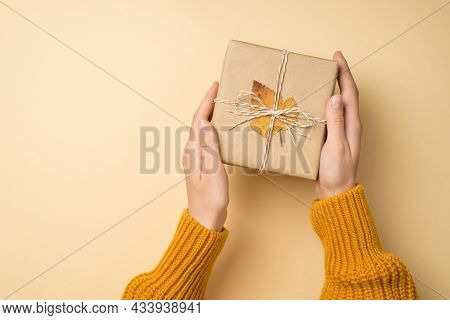 First Person Top View Photo Of Young Girl Hands In Yellow Knitted Sweater Holding Craft Paper Giftbo