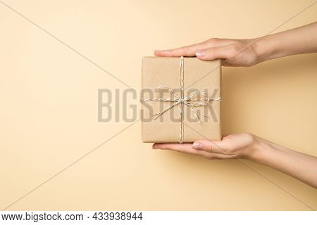 First Person Top View Photo Of Hands Holding Stylish Craft Paper Giftbox With Twine Bow On Isolated