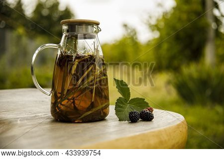 Warm Glass Teapot, Green Tea Leaves And Lemongrass On The Wooden Desk At Morning.