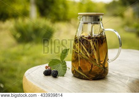 Warm Glass Teapot, Green Tea Leaves And Lemongrass On The Wooden Desk At Fall Day.