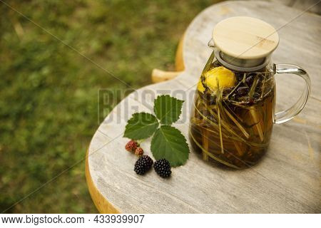 Warm Glass Teapot, Green Tea Leaves And Lemongrass On The Wooden Desk At Fall Day. Closeup Image.
