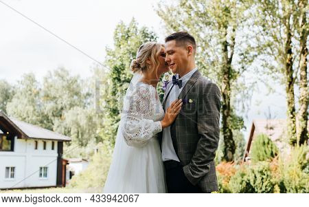 Young Loving Married Couple Hugs Outdoors, Beautiful Newlyweds Caress Each Other, Bride In Awhite Dr