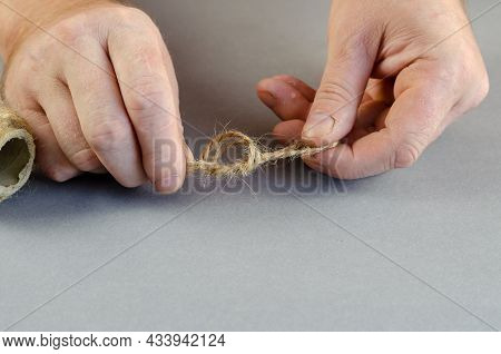 An Adult Male Ties A Knot Of Twine On A Gray Background. Hands Holding A Thin Twisted Thread Of Line