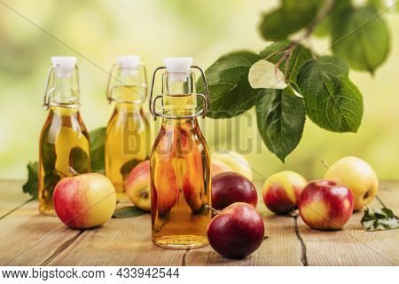 Bottle Of Apple Organic Vinegar Or Cider On Kitchen Table Background. Healthy Organic Drink.