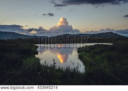 Yellow Big Cloud In Form Of Explosion Above Mountain Lake Near Green Grass On Foreground. Awesome Gi