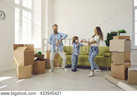 Happy Mum, Dad And Child Dancing And Having Fun In Their New House On Moving Day
