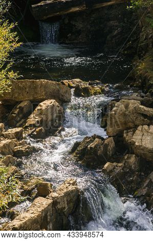 Cascade Of Small Beautiful Waterfalls On The Rocks With Sunlight.