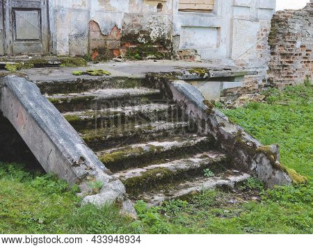 Stone Stairs Are Falling Apart. Old Steps Covered By Green Moss And Lichens. Destroyed Entrance Of A