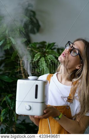 Young Woman Florist Holding Steaming Air Humidifier In Indoor Garden To Save Houseplants While Heati