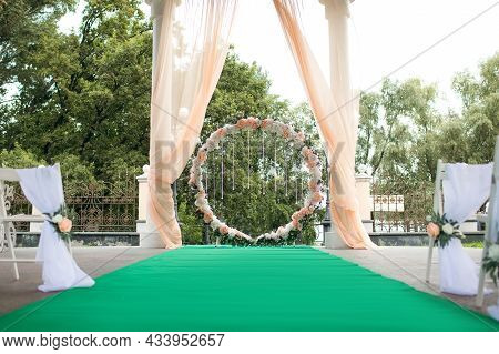 Round Wedding Arch For Wedding Ceremony With Flowers And Crystal Pendants With Green Carpet For Brid
