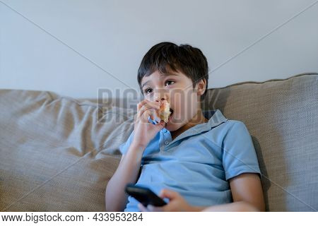 Happy Boy Bitting Red Apple While Wathing Cartoon On Tv, Mixed Race School Kid Relaxing At Home Afte