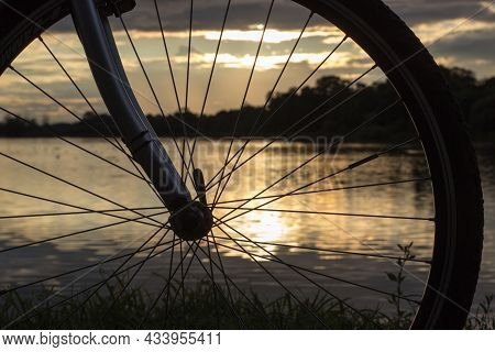 View Through A Bicycle Wheel On The Reflection Of The Setting Sun In The Lake
