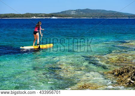 Young Active Girl On A Sup Board With A Paddle In Her Hand - Shot From The Back, Calm Surface Of The