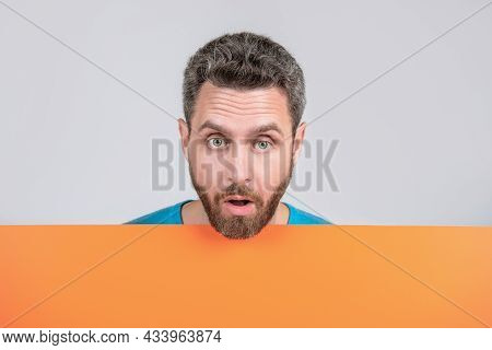 Surprised Mature Bearded Man Behind Orange Black Paper Banner With Copy Space For Info, Salesperson