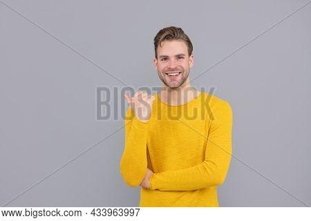 Advertising. Advertising Man. Happy Guy Point Finger Aside Grey Background