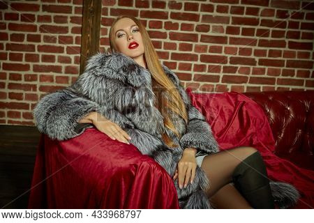 Bright blonde woman in an expensive silver fox fur coat sitting on a leather sofa covered with a velvet fabric. Luxury lifestyle. Fur coat fashion.