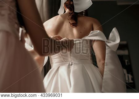 A Bride Wears A White Wedding Dress In A Hotel Room. The Bridesmaid Or Mom Helps To Lace Up The Brid