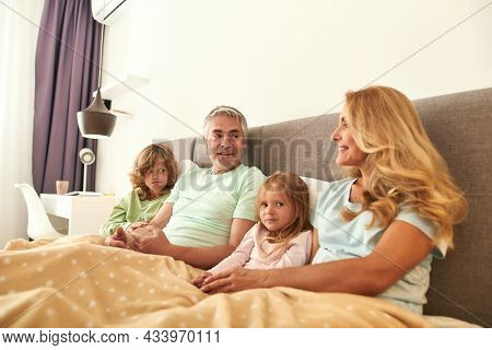 Smiling Caucasian Family With Two Kids Stay In Bed Relax On Weekend At Home Together. Happy Parents