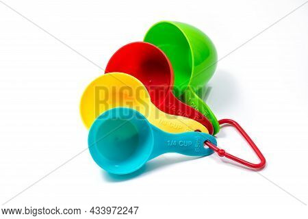 Four Pieces Of Colorful Ingredient Measuring Scoops Or Spoons Of Different Cup Sizes Connected Toget