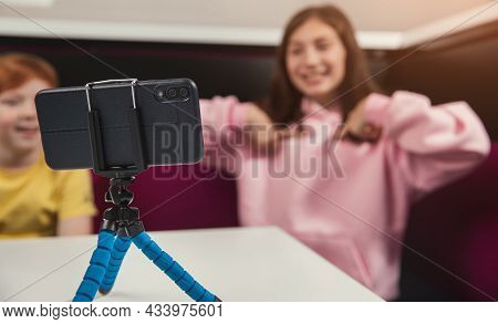 Cheerful Preteen Girl Sitting At Table With Friend And Pointing At Herself While Recording Vlog On M