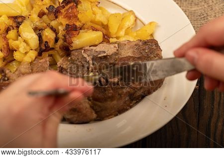 Someone Is Cutting A Piece Of Juicy Roast Meat On A Plate Of Fried Potatoes With A Knife And Fork. C
