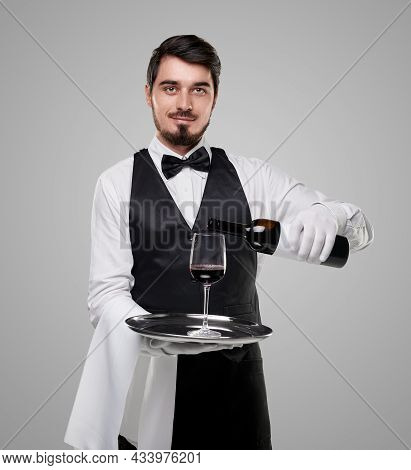 Young Bearded Waiter In Classic Uniform Holding Tray With Wineglass While Serving Red Wine From Bott