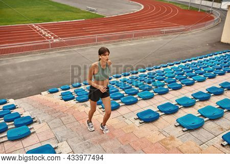 Motivated Young Female Runner Keeping Herself Fit, Training On The Stadium Outdoors. Sports, Healthy